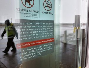 A security officer walks near a notice prohibiting marijuana possession at Denver International Airport
